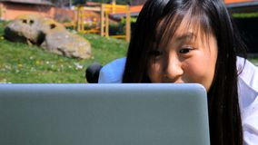 Happy asian woman chatting with pc in park stock video footage