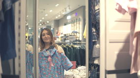 Happy asian woman choosing clothes and looking to mirror in mall or clothing store stock video