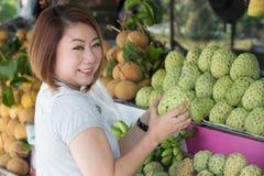 Happy asian woman choosing fresh custard apple fruit Stock Photos