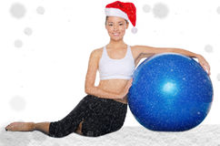 Happy asian woman in christmas cap with fitball under snow Royalty Free Stock Images