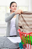 Woman having laundry at home. Happy asian woman doing the laundry at home royalty free stock images
