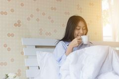 Happy Asian woman drinking coffee on bed. In the morning Royalty Free Stock Photos