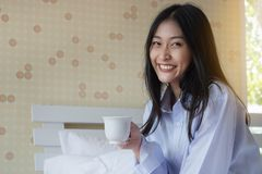 Happy Asian woman drinking coffee on bed. In the morning Stock Image