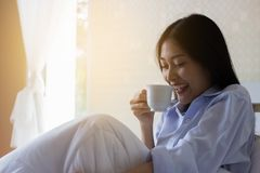 Happy Asian woman drinking coffee on bed. In the morning Stock Photos