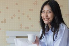 Happy Asian woman drinking coffee on bed. In the morning Stock Photography