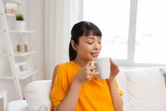 Happy asian woman drinking tea or coffee at home. People and leisure concept - happy asian woman drinking tea or coffee at home Stock Photo