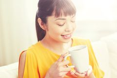 Happy asian woman drinking from tea cup. People, drinks and leisure concept - happy asian woman sitting on sofa and drinking tea from cup or mug at home Royalty Free Stock Photo