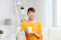 Happy asian woman drinking from tea cup Royalty Free Stock Images