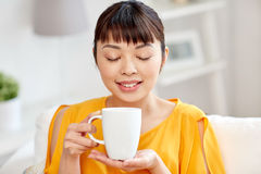 Happy asian woman drinking from tea cup Stock Photo