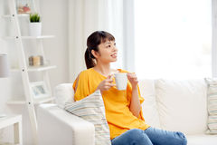 Happy asian woman drinking from tea cup Royalty Free Stock Photos