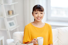 Happy asian woman drinking from tea cup Royalty Free Stock Photography