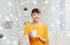 Happy asian woman drinking from tea cup. People, drinks and leisure concept - happy asian woman sitting on sofa and drinking tea from cup or mug at home over Royalty Free Stock Photo
