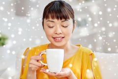 Happy asian woman drinking from tea cup. People, drinks and leisure concept - happy asian woman sitting on sofa and drinking tea from cup or mug at home over Stock Photos