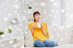 Happy asian woman drinking from tea cup. People, drinks and leisure concept - happy asian woman sitting on sofa and drinking tea from cup or mug at home over Royalty Free Stock Image