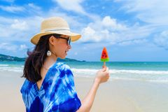 Happy Asian woman eating watermelon ice cream at the beach during travel holidays vacation outdoors at ocean or nature sea at noon. Phuket, Thailand stock photos