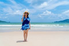 Happy Asian woman eating watermelon ice cream at the beach during travel holidays vacation outdoors at ocean or nature sea at noon. Phuket, Thailand stock images