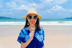 Happy Asian woman eating watermelon ice cream at the beach during travel holidays vacation outdoors at ocean or nature sea at noon. Phuket, Thailand royalty free stock photography