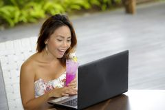 Happy Asian woman in elegant and sexy dress sitting outdoors at pool resort coffee shop having healthy fruit juice working on lapt Stock Photos