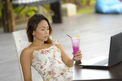 Happy Asian woman in elegant and sexy dress sitting outdoors at pool resort coffee shop having healthy fruit juice working on lapt Stock Images