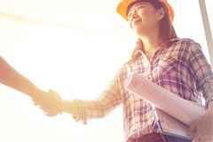 Happy Asian woman engineer as construction workers with blueprint royalty free stock images