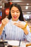Asian woman enjoying Chinese food in Chinese restaurant. Happy asian woman enjoying Chinese food in Chinese restaurant Stock Photography
