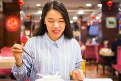 Asian woman enjoying Chinese food in Chinese restaurant. Happy asian woman enjoying Chinese food in Chinese restaurant Stock Images