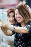 Happy asian woman with friend taking a selfie Stock Image