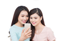 Happy asian woman friends taking a self portrait with a cell pho Royalty Free Stock Photography
