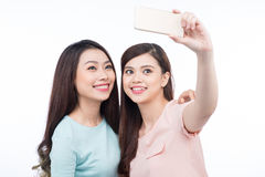 Happy asian woman friends taking a self portrait with a cell pho Stock Photography