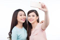 Happy asian woman friends taking a self portrait with a cell pho. Happy asian women friends taking a self portrait with a cell phone Stock Photography