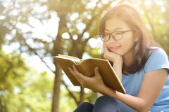 Asian woman in Blue shirt reading a book. Happy Asian woman with Glasses in Blue shirt reading a book on Green natural background. Girl is smiling at Outdoor Stock Image