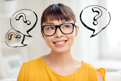 Happy asian woman in glasses over question marks Stock Photos