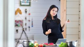 Happy Asian woman having fun and dancing at kitchen during cooking fresh organic meal stock video footage
