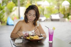 Happy Asian woman on her 20s enjoying healthy food for brunch breakfast or lunch sitting at coffee shop Royalty Free Stock Photography