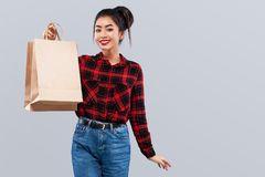 Happy asian woman hipster at shopping holding bag isolated on gray background on black friday holiday. Copy space for. Beautiful young woman make shopping in royalty free stock photos