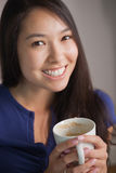 Happy asian woman holding mug of coffee looking at camera Royalty Free Stock Images