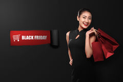 Happy asian woman holding paperbag with Black Friday text Royalty Free Stock Photography
