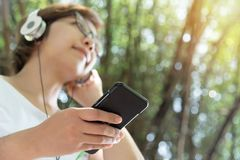 Woman listening to the music with headphone and smart phone. royalty free stock photo