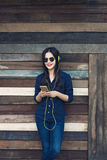 Happy asian woman listening to music on her headphone and holdin Royalty Free Stock Photography