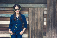 Happy asian woman listening to music on her headphone and holdin Royalty Free Stock Photo