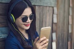 Happy asian woman listening to music on her headphone and watchi Stock Photography