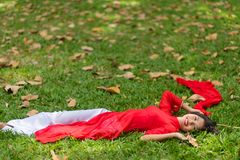 Happy Asian Woman Lying Down on Grassland Royalty Free Stock Photography