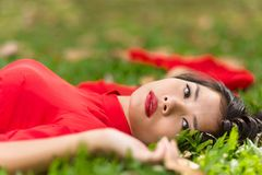Happy Asian Woman Lying Down On Grassland Stock Images