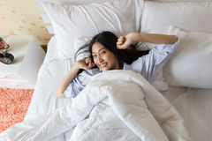 Happy Asian woman in the morning. On bed Royalty Free Stock Image