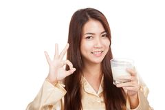 Happy Asian woman in pajamas drink milk show OK sign Royalty Free Stock Image