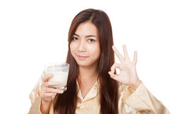 Happy Asian woman in pajamas drink milk show OK sign Royalty Free Stock Photography