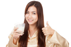 Happy Asian woman in pajamas drink milk show thumbs up Royalty Free Stock Photo