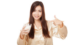 Happy Asian woman in pajamas point to glass of  milk Royalty Free Stock Photography