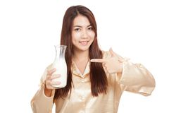 Happy Asian woman in pajamas point to milk bottle Stock Photography