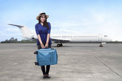 Happy asian woman passenger wearing hat holding suitcase Royalty Free Stock Image